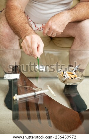 Addict at home using cocaine, pot, and injectible drugs.   - stock photo