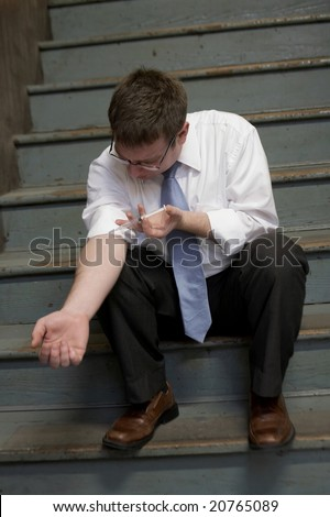 Addict in suit injecting needle into arm - stock photo