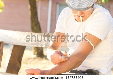 Addicted jobless middle-aged man Injecting a drug intravenously into his left arm sitting on a bench outdoors - stock photo
