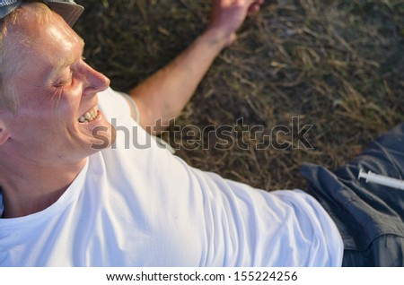 Addicted man laughing lying down on grass while experiencing euphoria caused by heroin - stock photo