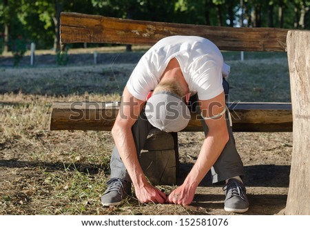Addicted man sitting on a bench in the park while feeling sick and experiencing nausea after drug use - stock photo
