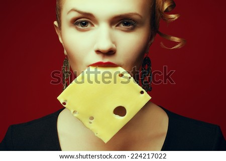 Addicted to cheese concept. Arty portrait of fashionable young woman with golden earrings holding square slice of cheese in her mouth and posing over red background. High fashion style. Studio shot