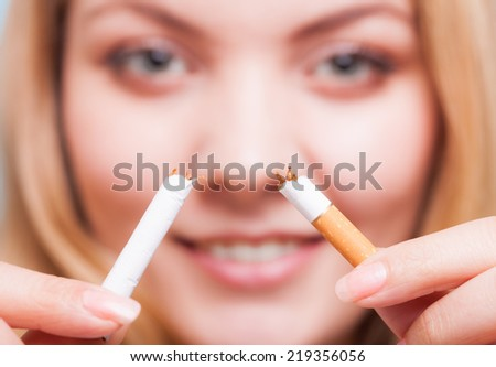 Addiction. Closeup of young woman determined girl breaking the cigarette. Quit smoking. Studio shot.