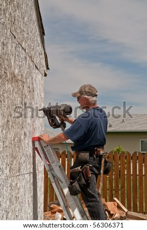 Adding a few nails to the side of an old outbuilding prior to siding it - stock photo