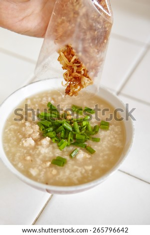 adding fried onion to  chicken porridge - stock photo