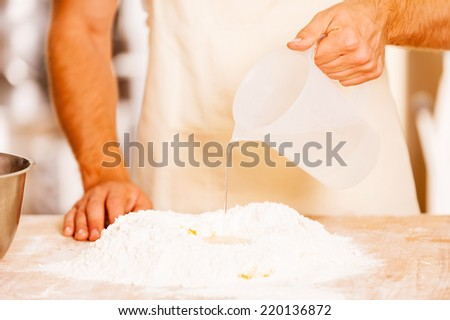 Adding some water to flour. Close-up of male baker pouring water on the flour  - stock photo