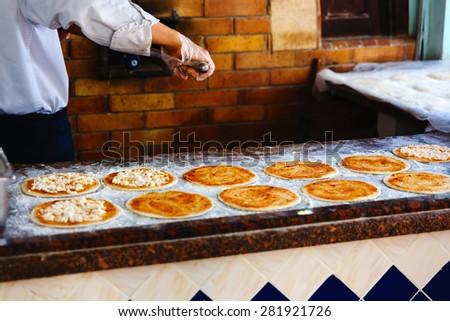 adding tomato sauce to pizza base in arabic restaurant - stock photo