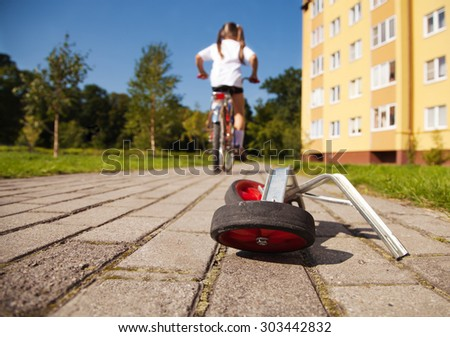additional wheels of the bike lying on the road. girl rides a bicycle away - stock photo