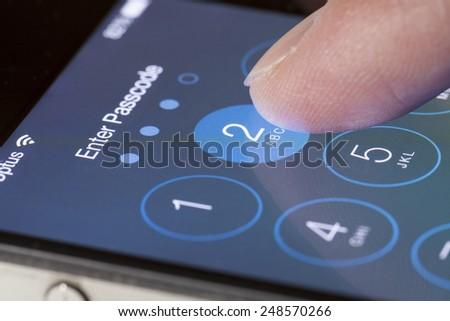 Adelaide, Australia - September 20, 2013: Entering passcode on an iPhone running iOS. iOS is the foundation of iPhone, iPad, and iPod touch. It comes with a collection of apps and useful features.  - stock photo