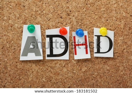 ADHD the abbreviation for Attention Deficit Hyperactivity Disorder in cut out magazine letters pinned to a cork notice board.  - stock photo