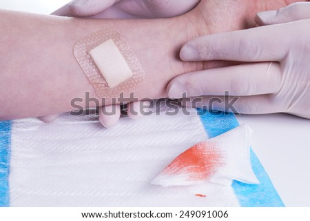 Adhesive Bandage. Bandaging at Wound by the Doctor - stock photo