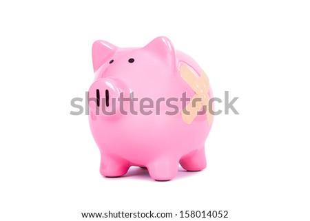 Adhesive bandage, plaster on pink piggy bank, isolated on white background. - stock photo