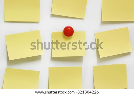Adhesive note and red magnet button on whiteboard.