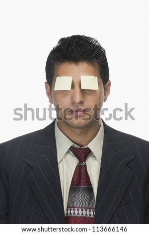 Adhesive notes on a businessman's eyes - stock photo