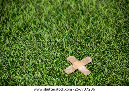 Adhesive plasters sticked to green grass - stock photo