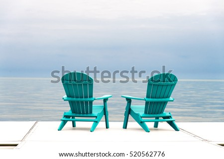 Adirondack Chairs At The End Of A Pier Overlooking A Large Blue Lake With A  Blue