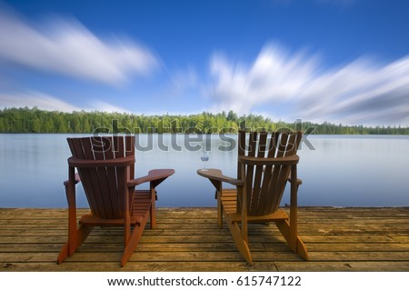 Adirondack Chairs On A Lake Deck Two Adirondack Chairs Sitting On A Wood  Dock Facing A