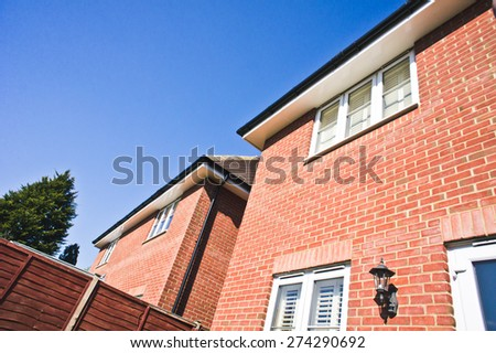 Adjacent detached modern houses in the UK on a sunny day - stock photo