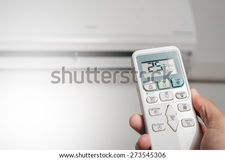 adjust air conditioner to 25 degrees celsius with remote control - stock photo
