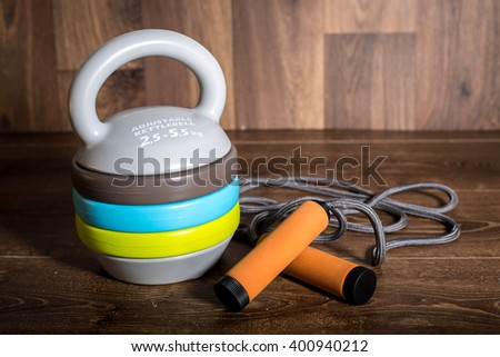Adjustable kettlebell, cycle gloves dumbbells and yoga mat on wooden background. Weights for a fitness training. - stock photo