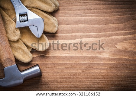Adjustable spanner claw hammer leather safety gloves on wooden board.
