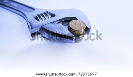 Adjustable wrench gripping a stack of coins with shallow depth of field. - stock photo