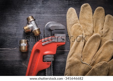 Adjustable wrench plumbing fittings protective gloves on wooden board. - stock photo