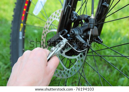 Adjusting Bicycle Gears with Pliers and Key - stock photo