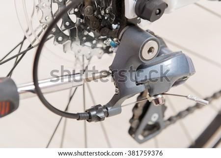 Adjusting bicycle's rear derailleur - stock photo