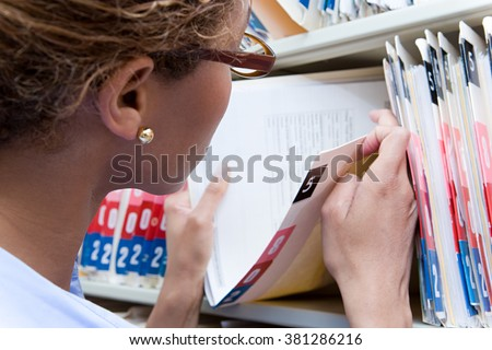 Administrator looking at medical record - stock photo