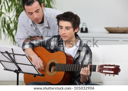 Adolescent boy learning to play the guitar - stock photo
