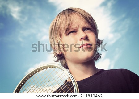 Adolescent boy with a tennis racket - stock photo