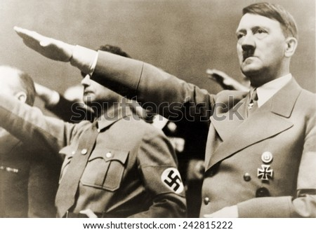 Adolf Hitler, giving Nazi salute. To Hitler's right is Rudolph Hess. 1939. - stock photo