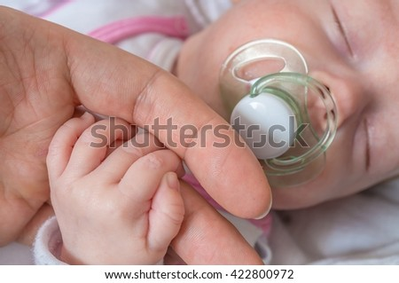 Adoption baby concept. Man is touching baby with hand. - stock photo