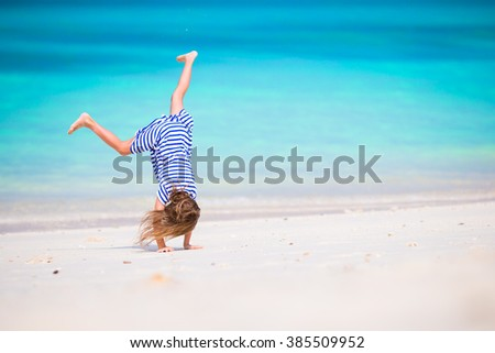 Adorable active little girl at beach during summer vacation - stock photo