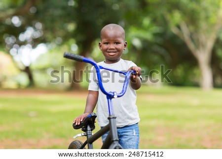 adorable african little boy with his bicycle at the park
