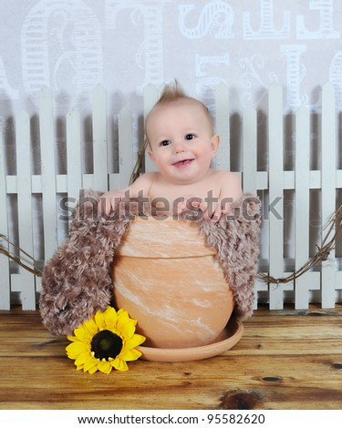 adorable and happy baby boy sitting in clay flower pot - stock photo