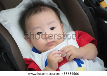 Adorable Asian boy lying on the baby seat