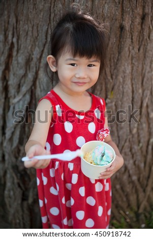 Adorable asian girl eating ice cream in the summer over a trunk of a tree background. Pretty child enjoy and relax in nature. Outdoors. - stock photo
