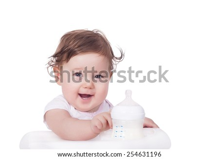 Adorable baby and baby bottle filled with milk - stock photo