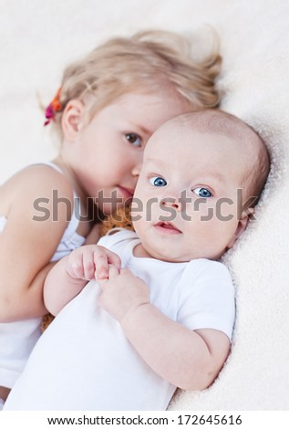 Adorable baby boy and her older sister on a white background - stock photo