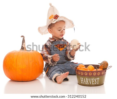 Adorable baby boy dressed as a scarecrow and playing with gourds and pumpkins.  Isolated on white with room for your text. - stock photo