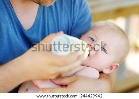 Adorable baby boy drinking milk from bottle in father hands  - stock photo