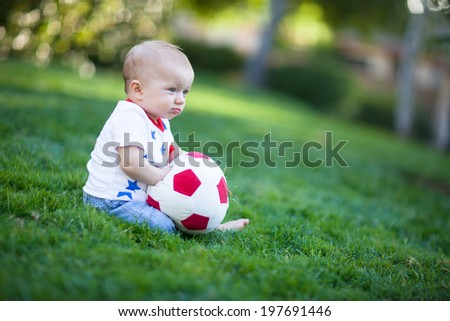 Adorable baby boy holding a red and white soccer ball