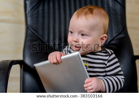 Adorable Baby Boy Holding his Tablet Computer While Sitting on an Office Chair and Looking at the Camera. - stock photo