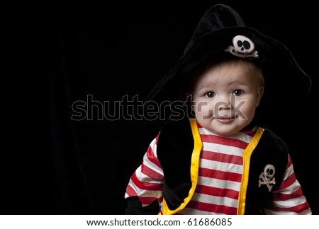 Adorable baby boy in a pirate costume for Halloween on a black background. - stock photo