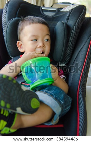 Adorable baby boy in safety car seat