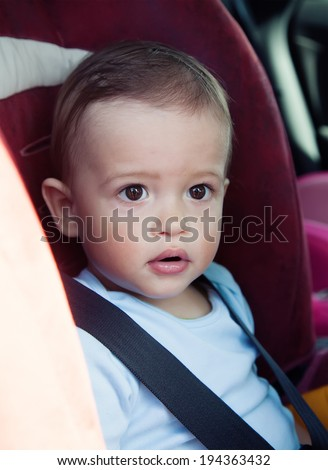 Adorable baby boy in safety car seat.  fearful glance - stock photo