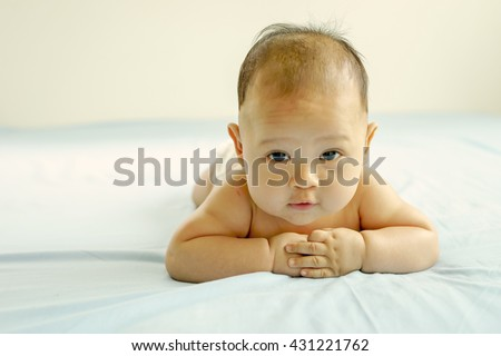 Adorable baby boy in white sunny bedroom. Newborn child relaxing in bed. Nursery for young children. Textile and bedding for kids. Family morning at home.  - stock photo
