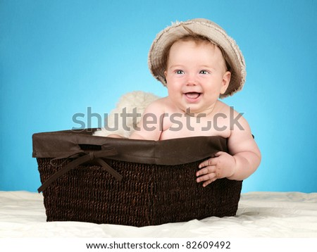 Adorable baby boy in wicker basket